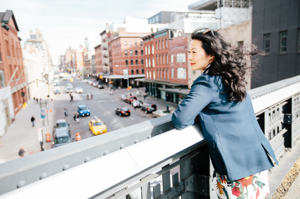 Woman looking over her shoulder while leaning on a bridge railing at the High Line in New York City, USA