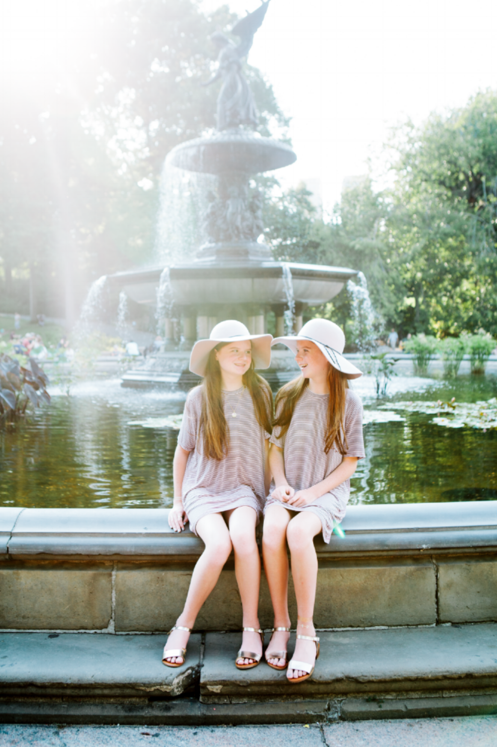 Twin sisters smiling at each other while sitting on the edge of Bethesda fountain in Central Park, New York City USA