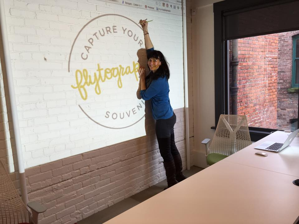 Michelle tracing our logo on the white brick wall, right before painting it on. We heart our office.