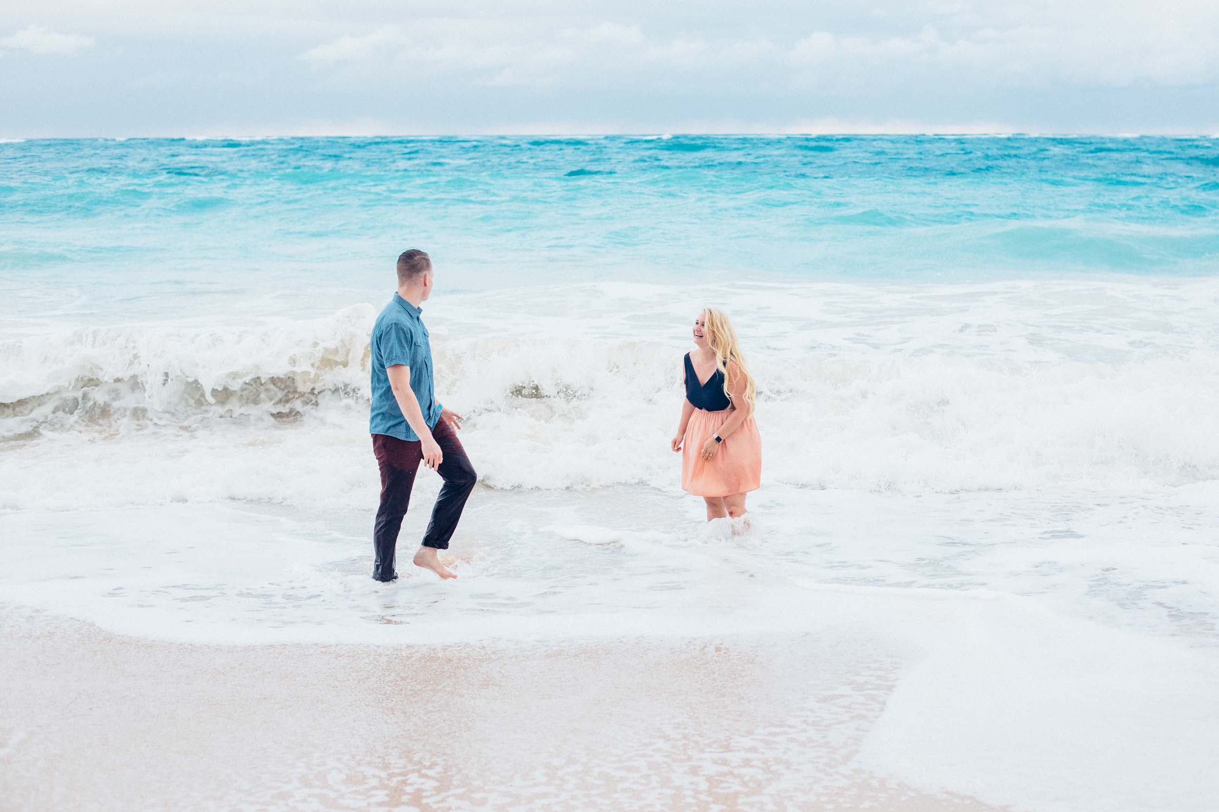 Couple playing in the shallow waves together in Maui, Hawaii USA