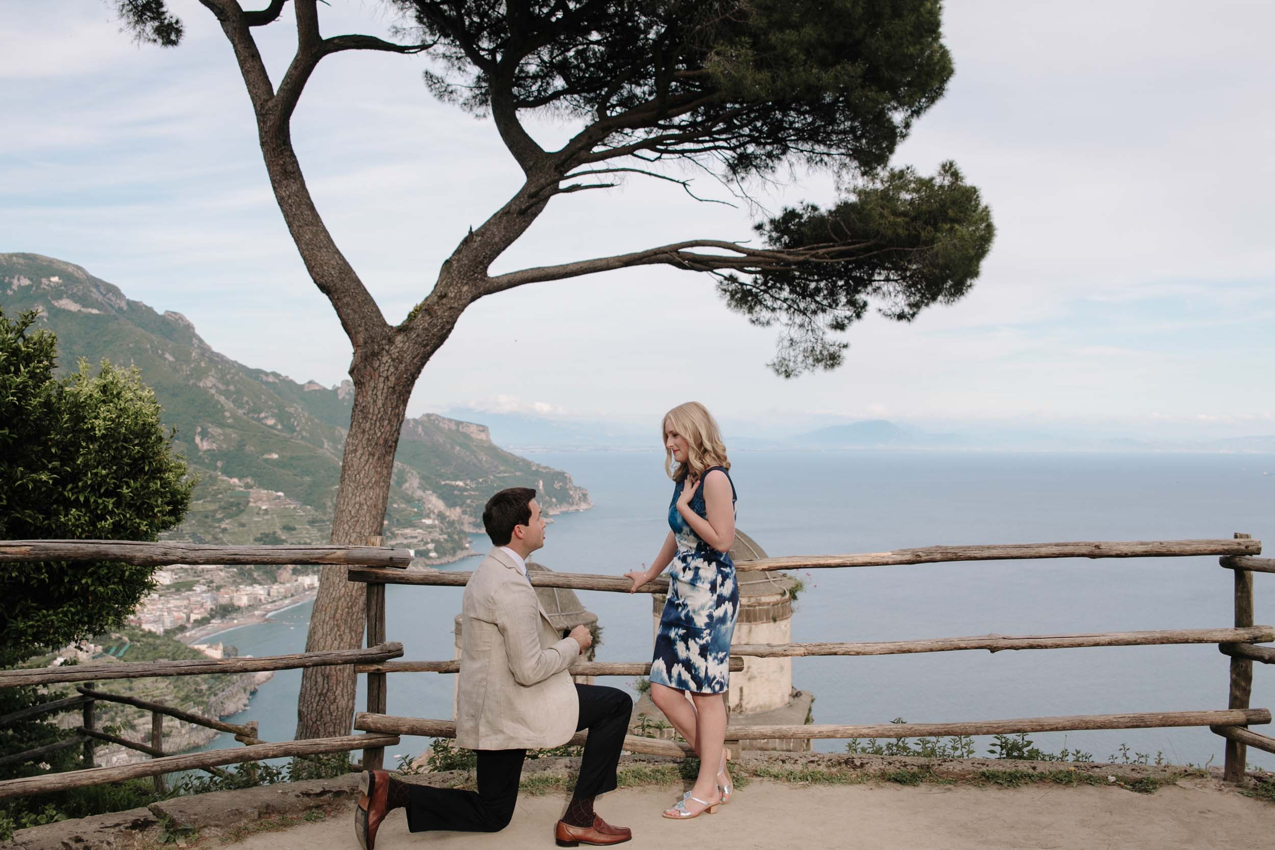 Man proposing to his partner with Amalfi coast in the background at Amalfi, Italy