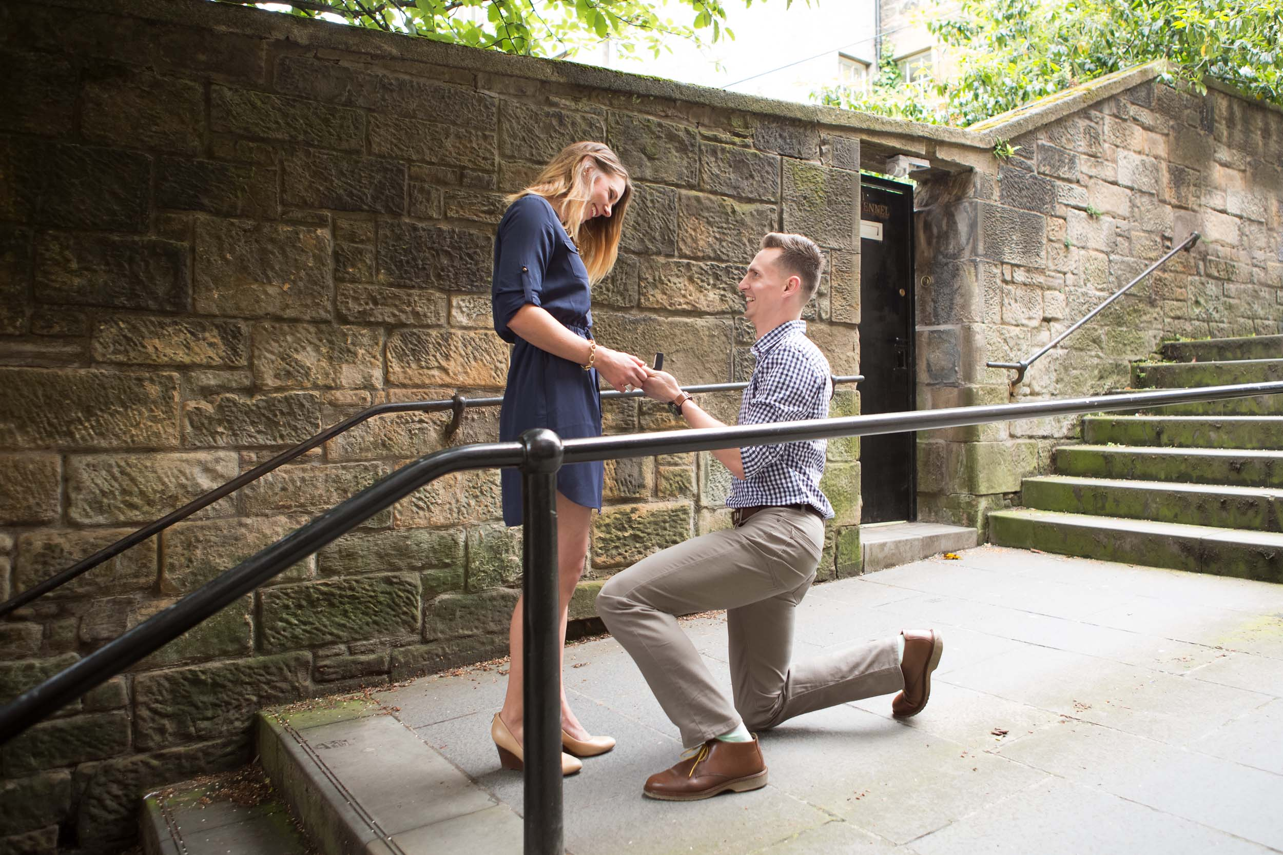Couple smiling lovingly at each other while the male partner proposes to his female partner in Edinburgh, UK