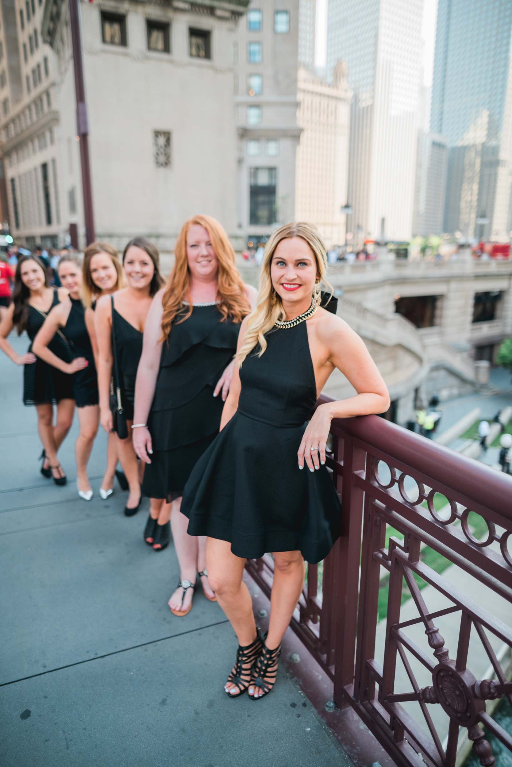 Six female friends on a bachelorette trip together standing one behind another on a bridge in Chicago, USA