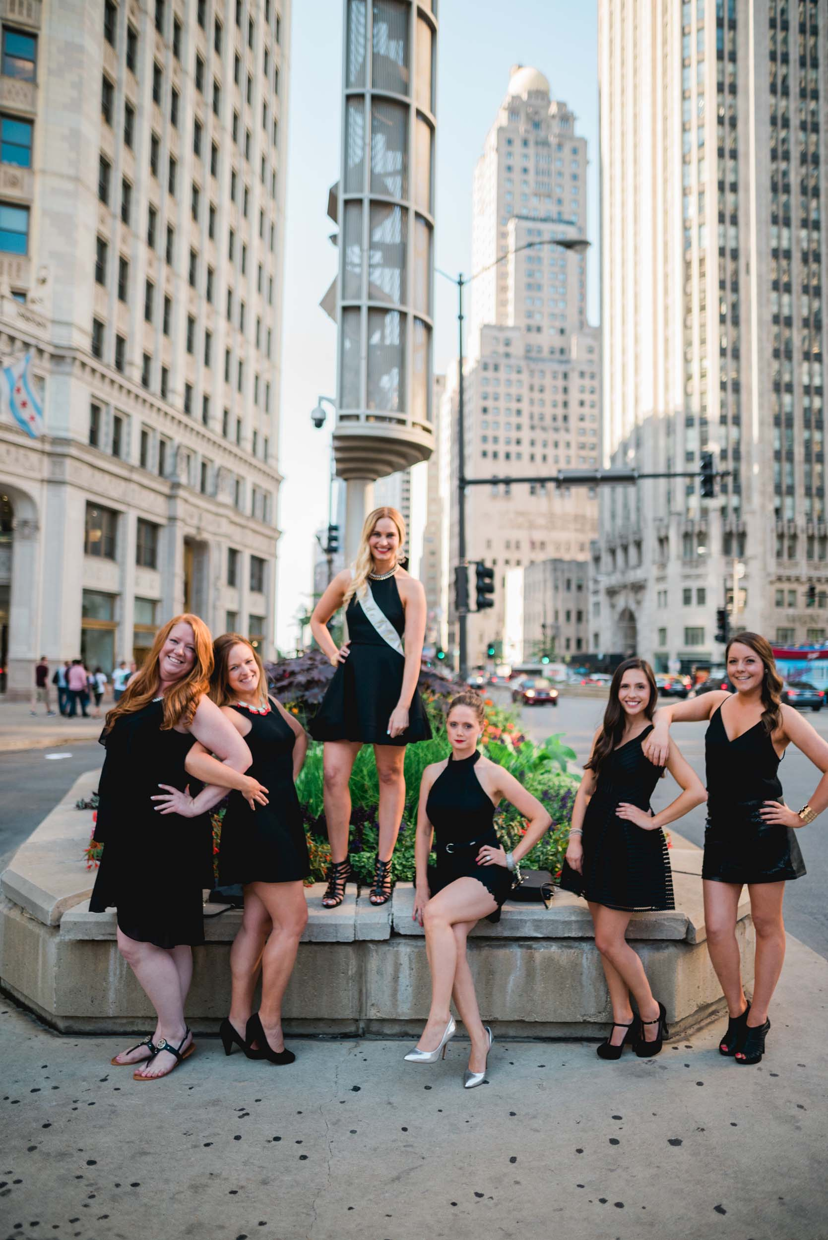 Six female friends on a bachelorette trip standing in a street meridian area together in Chicago, USA