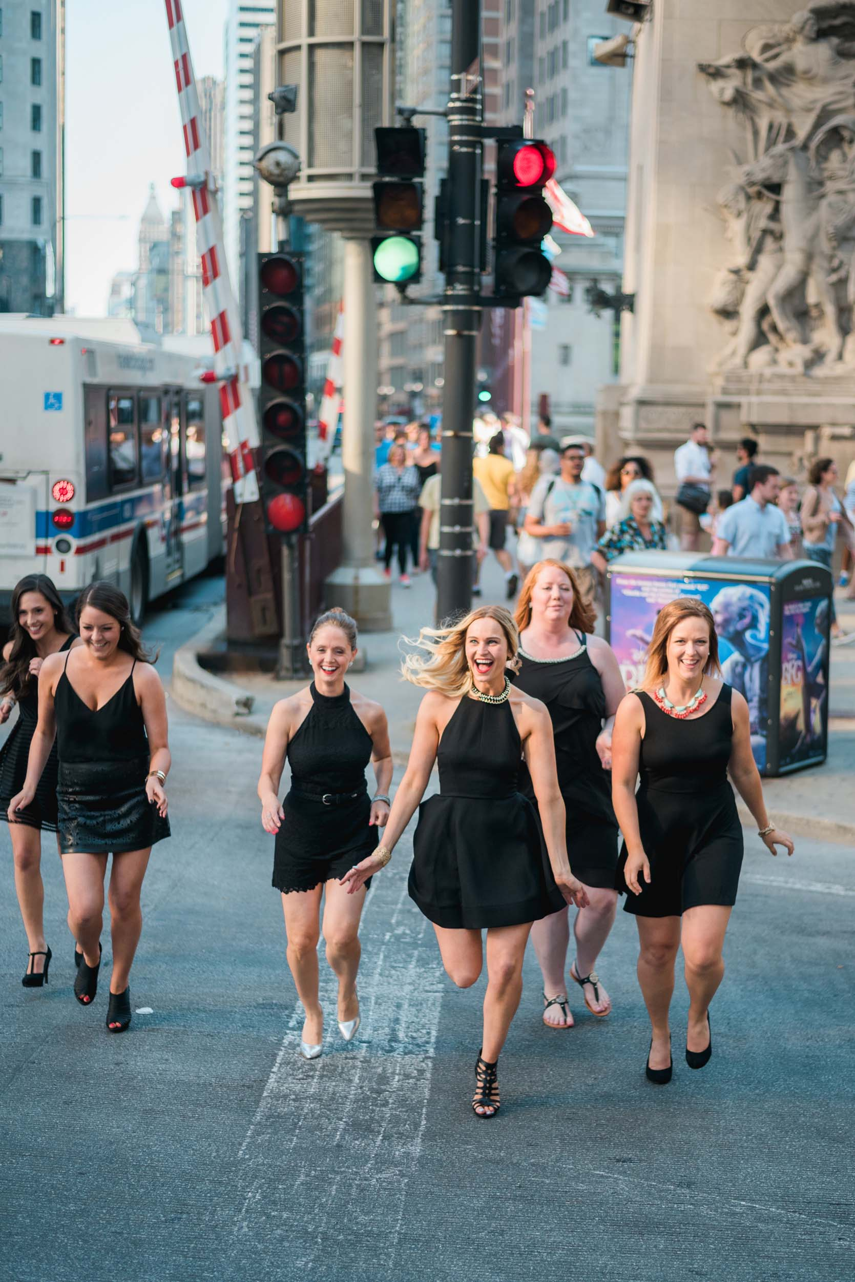 Six female friends on a bachelorette trip together crossing an intersection and laughing in Chicago, USA