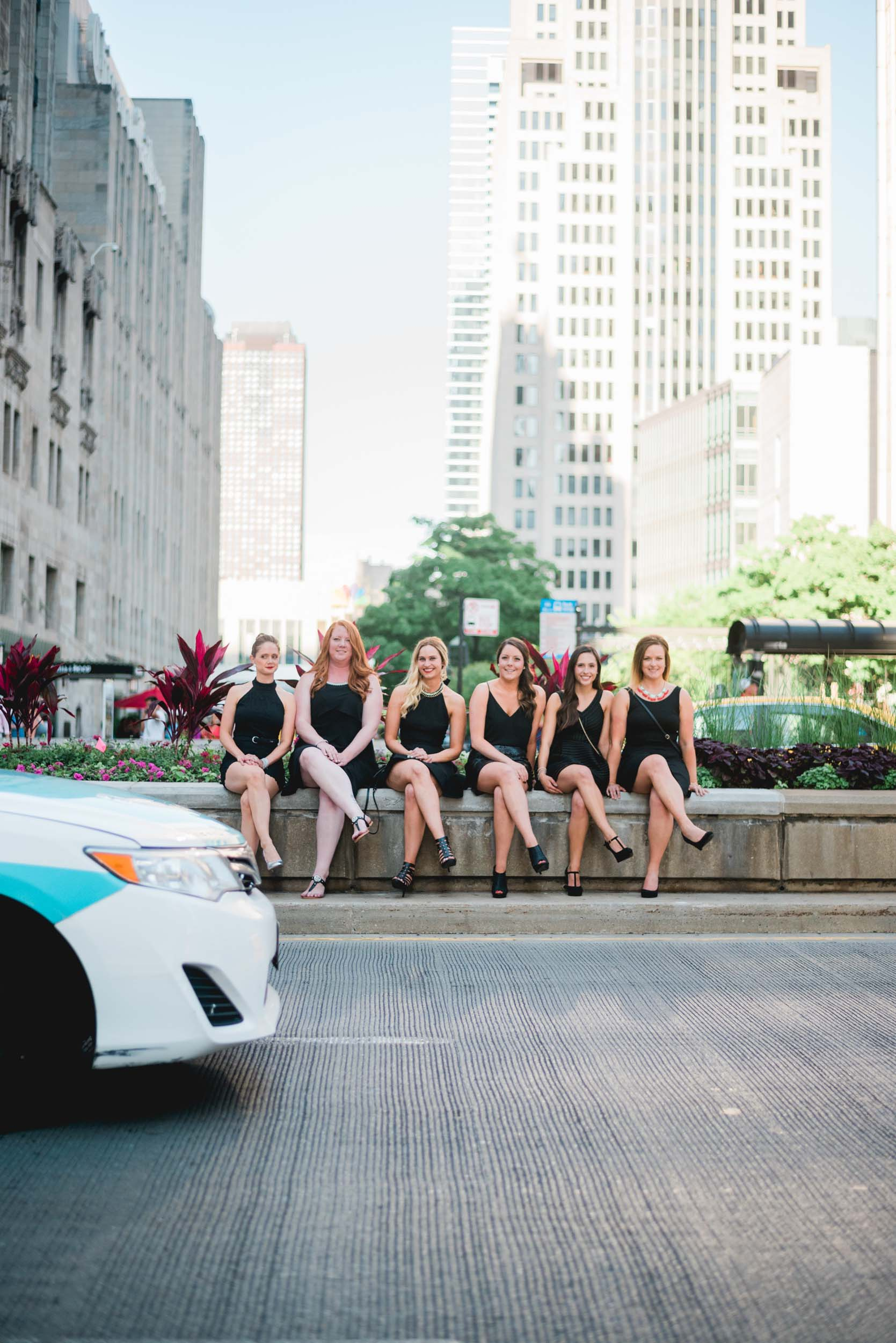 Six female friends on a bachelorette trip together sitting on a stone ledge along a sidewalk in Chicago, USA