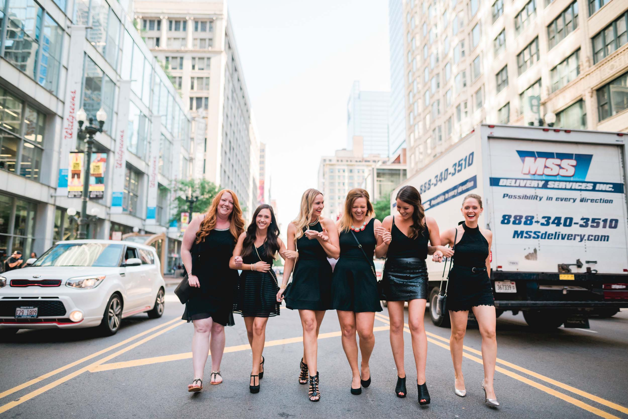 Six female friends walking together down a street on a bachelorette trip in Chicago, USA