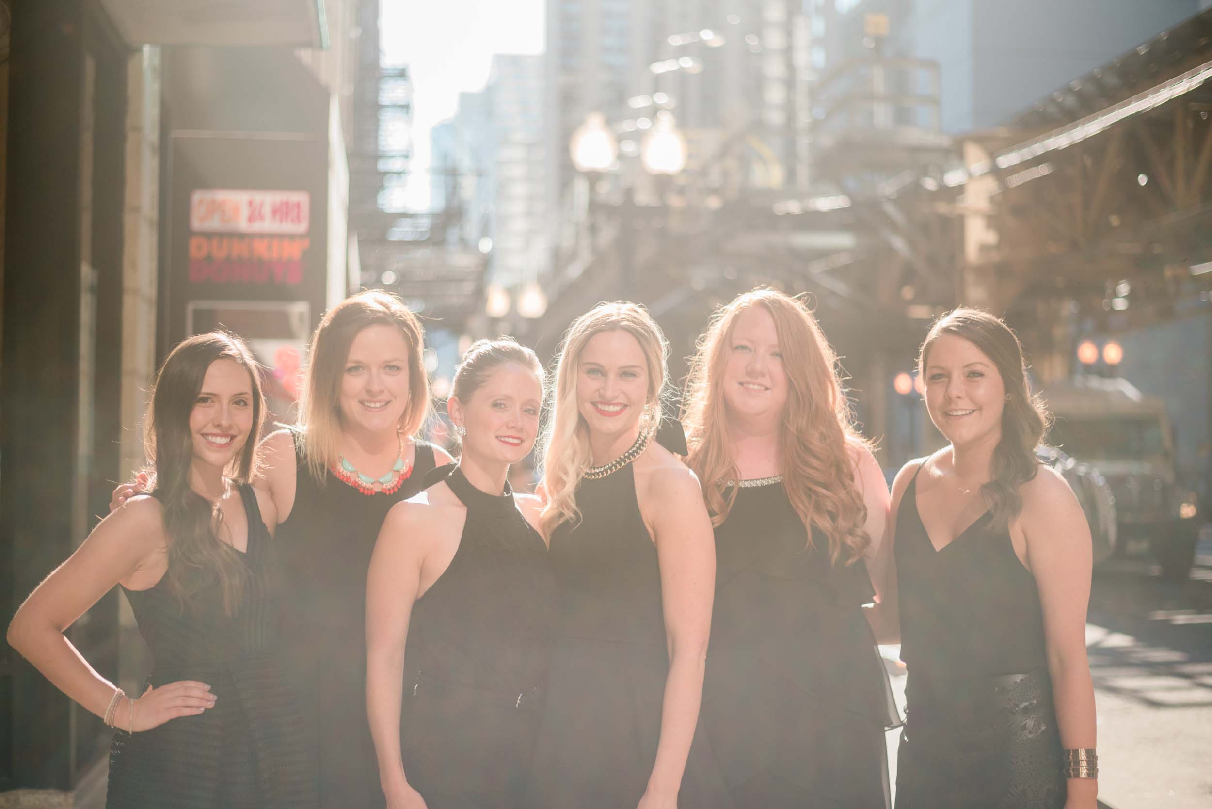 Six female friends standing together smiling on a bachelorette trip in Chicago, USA