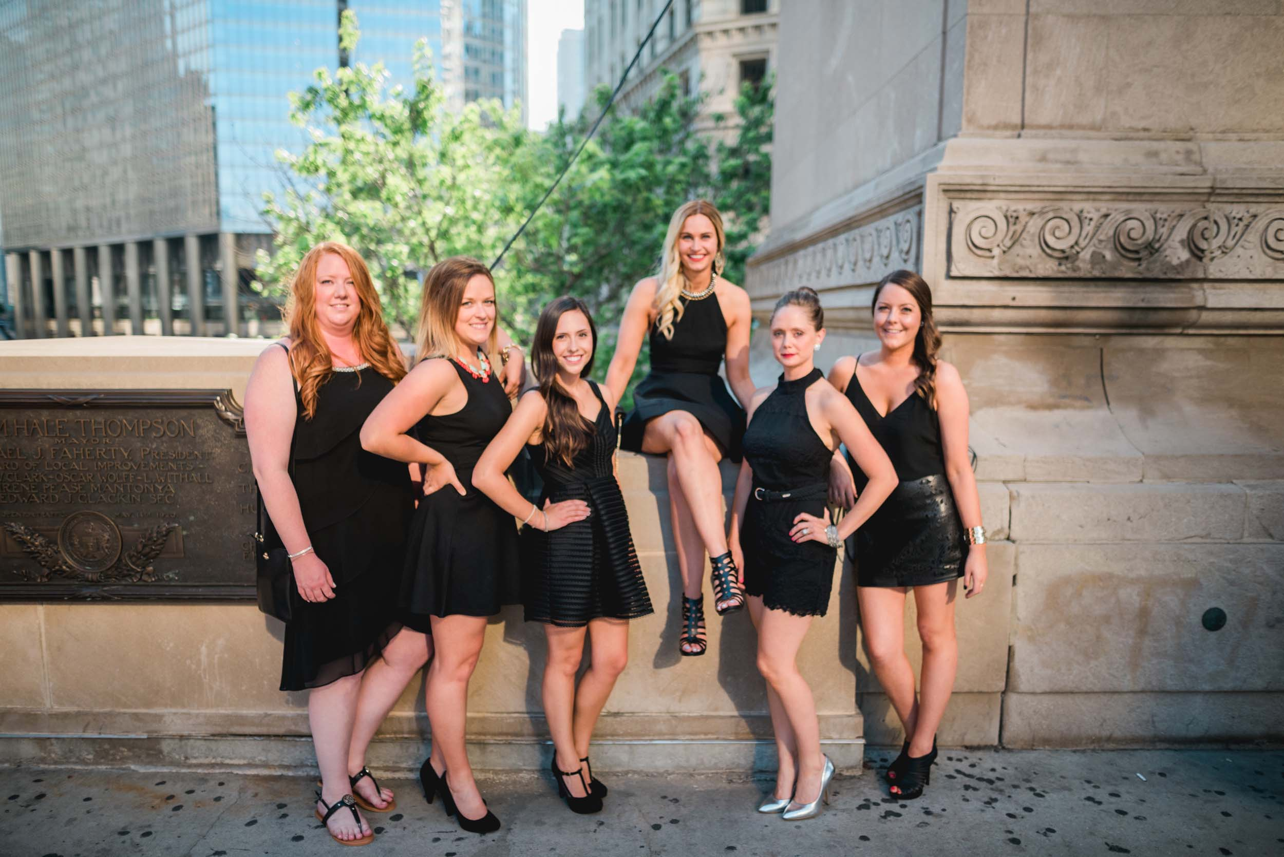 Six female friends standing together with bride-to-be sitting up on a ledge on a bachelorette trip in Chicago, USA