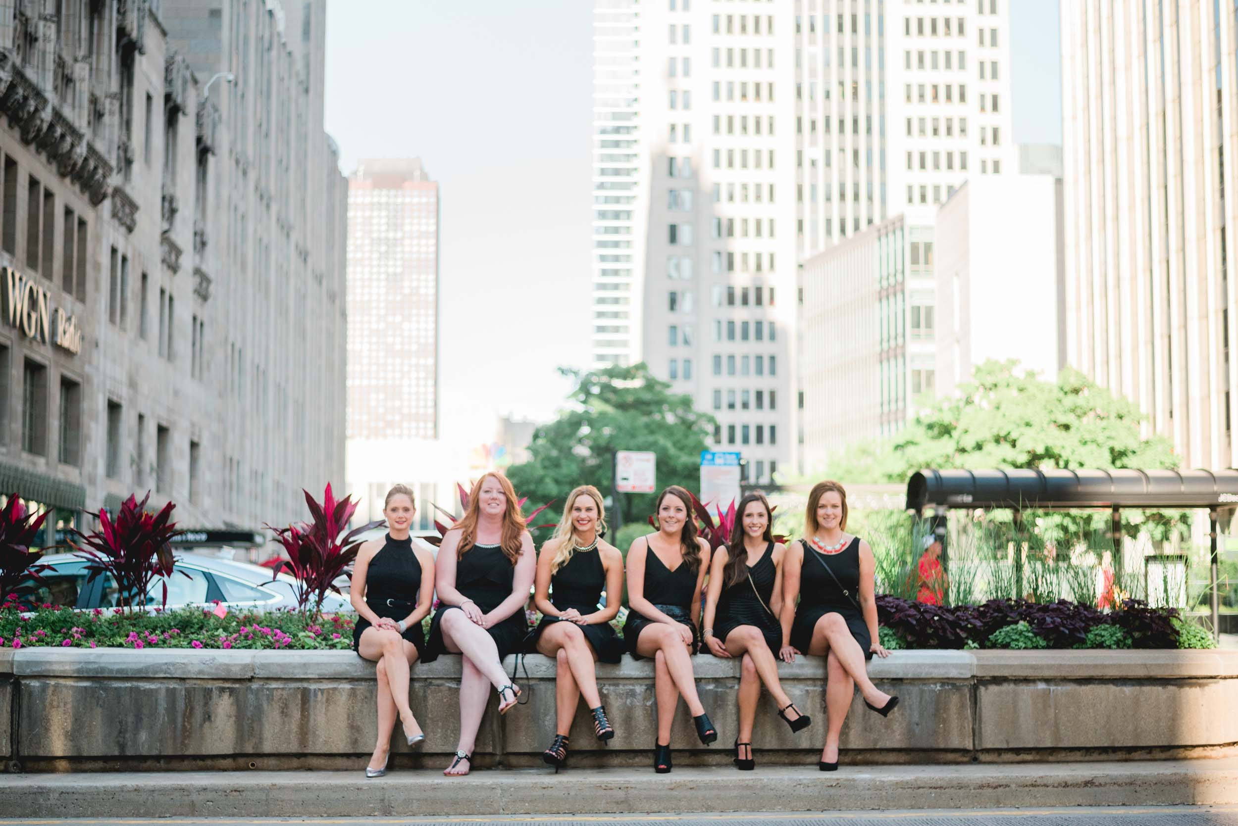 Six female friends sitting together on a stone ledge along a sidewalk on a bachelorette trip in Chicago, USA