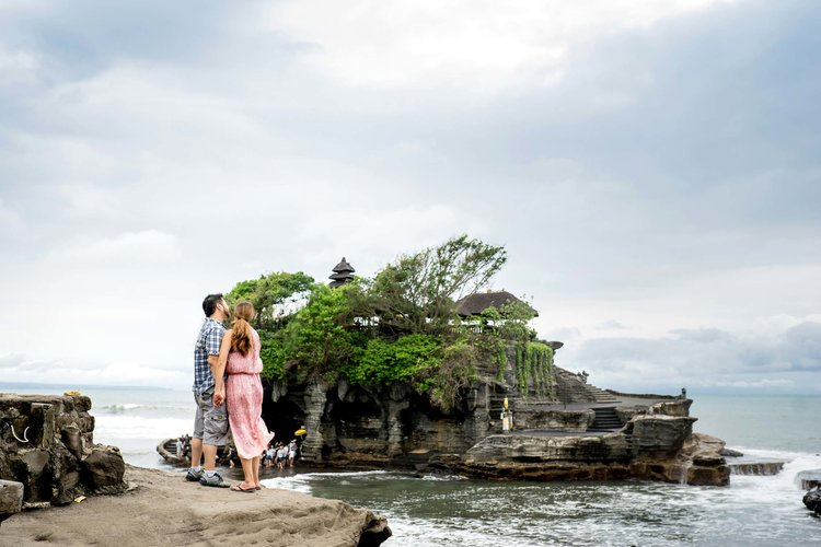 Couple holding hands and overlooking the Uluwatu Temple of Bali, Indonesia