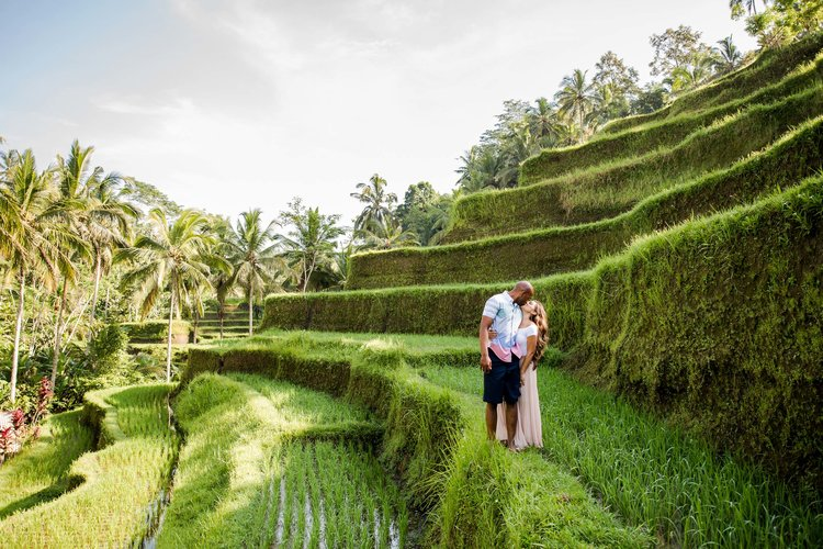 Couple standing in rice paddy field and kissing on a couples trip in Ubud, Bali Indonesia