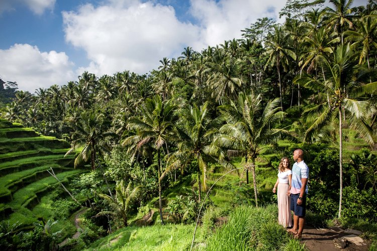 Couple standing overlooking the rice paddy fields on a couples trip in Ubud, Bali Indonesia