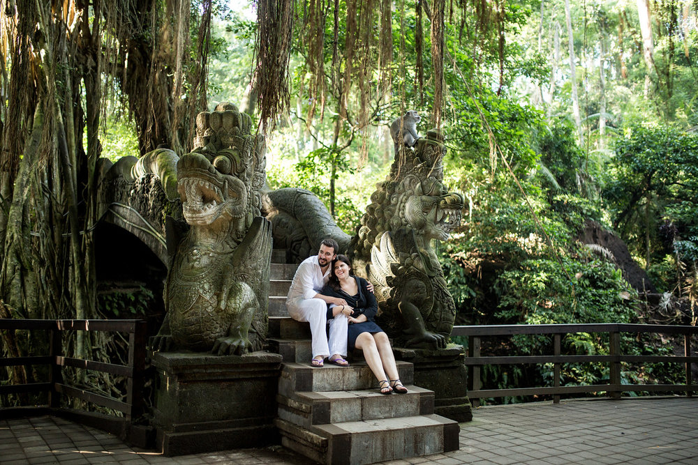 Couple sitting on steps of a bridge in the Monkey Forest in Bali, Indonesia