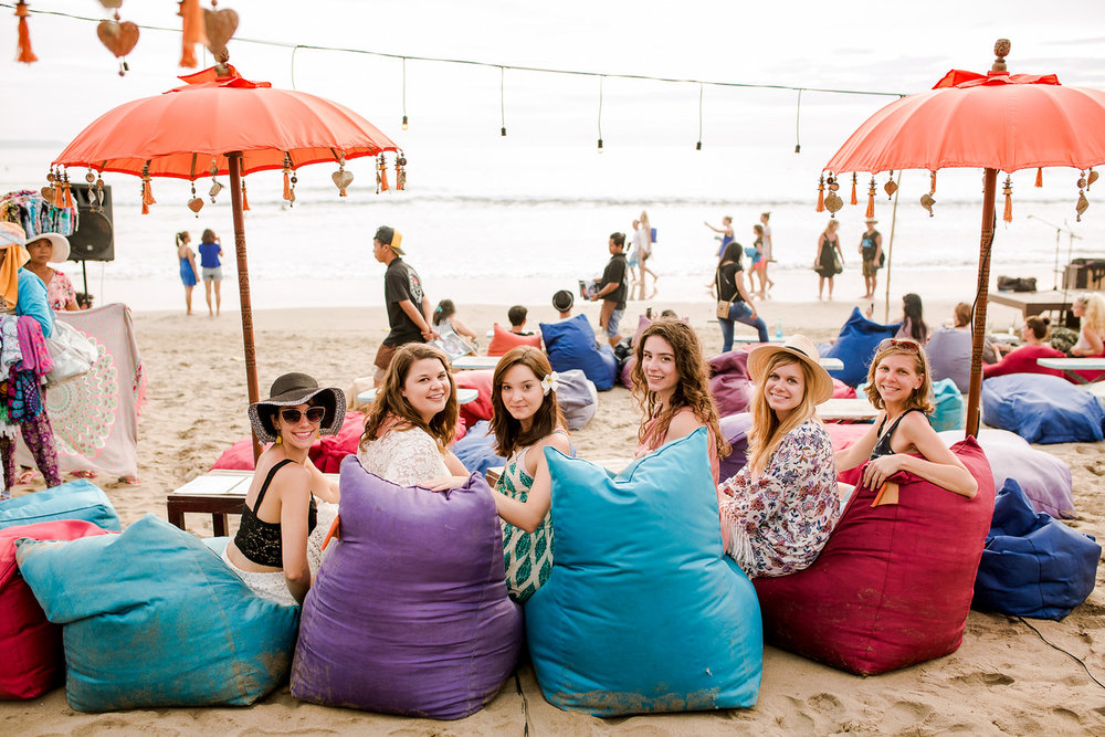 Large group of people on the beach sitting on bean bag chairs beneath umbrellas on Seminyak Beach, Bali