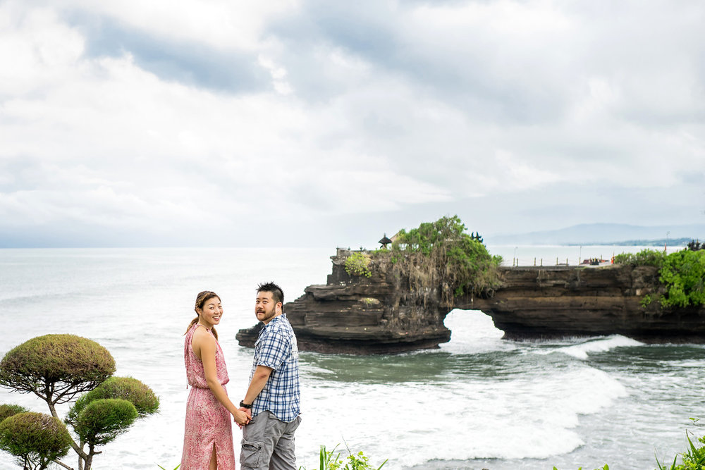 Couple holding hands and looking over their shoulders at the camera with the Uluwatu Temple in the background in Bali, Indonesia