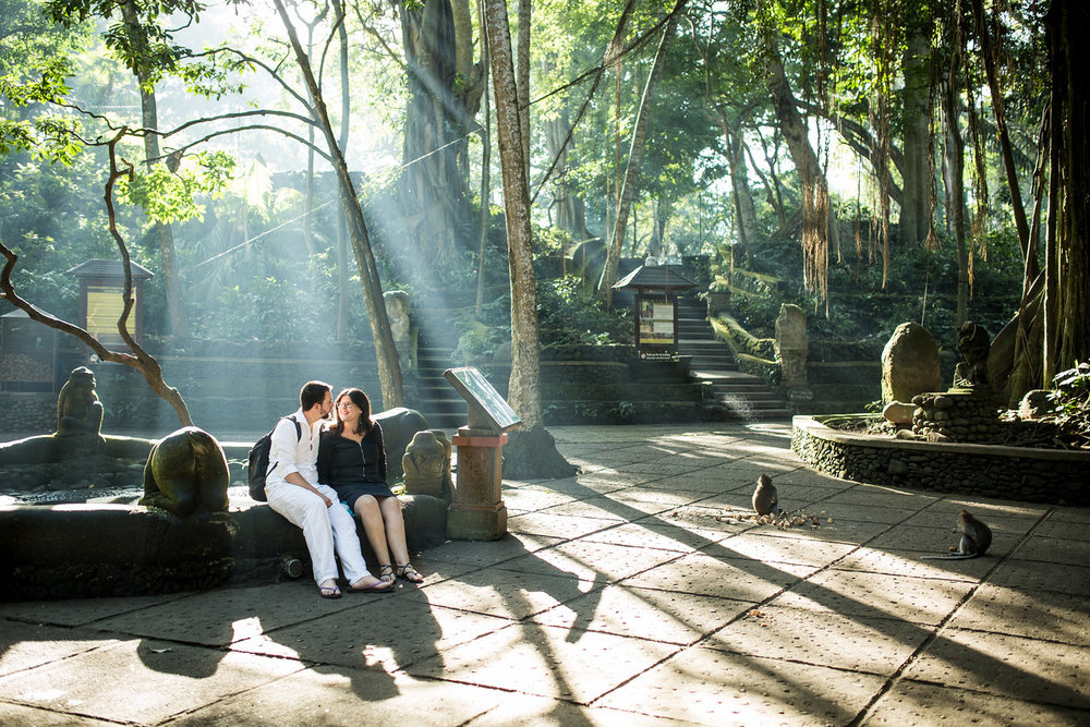 Couple sitting at the edge of a water pond together with monkeys nearby in the Monkey Forest in Bali, Indonesia