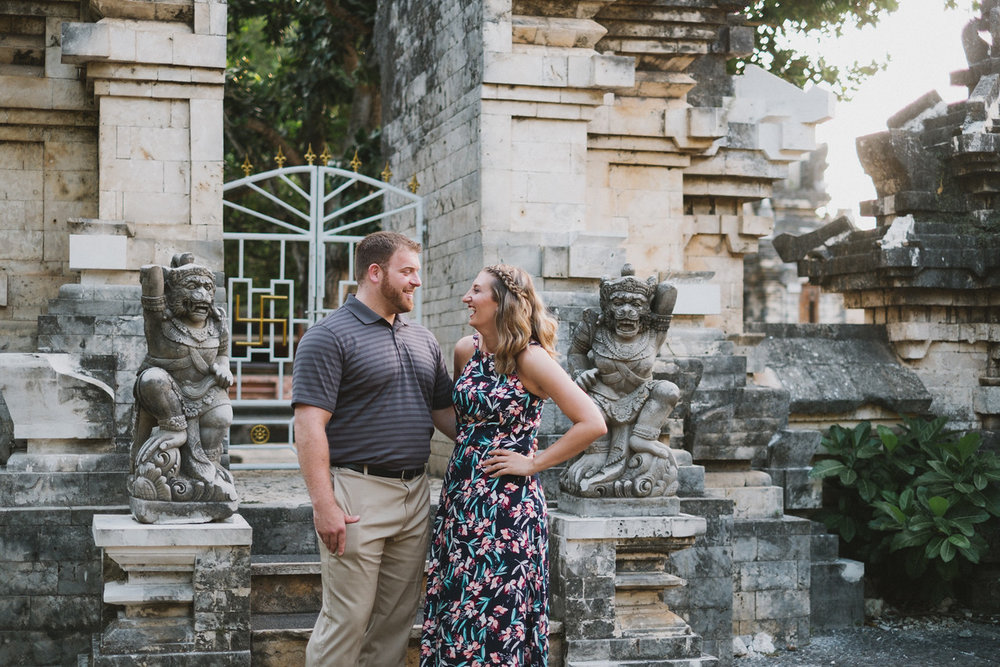Couple laughing with each other and standing outside of temple gates in Uluwatu, Bali Indonesia