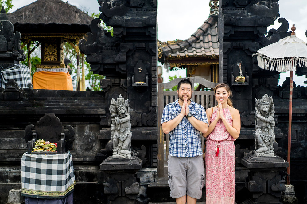 Couple standing outside of temple gates doing prayer hands in Uluwatu Temple, Bali Indonesia