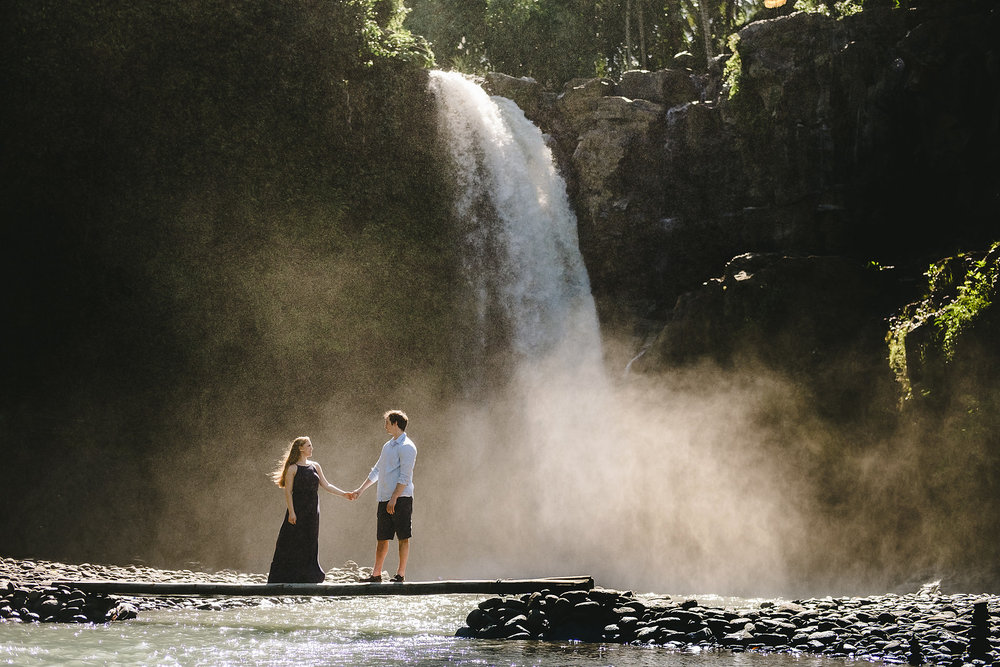 Couple walking across a wooden plank to cross over the water of the Tegenungan Waterfall in Bali Indonesia