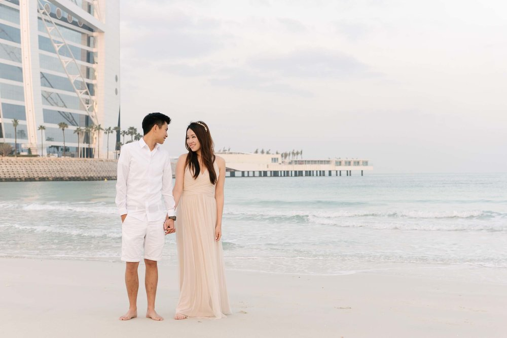 Couple holding hands and standing on Jumeirah Beach close to the water in Dubai