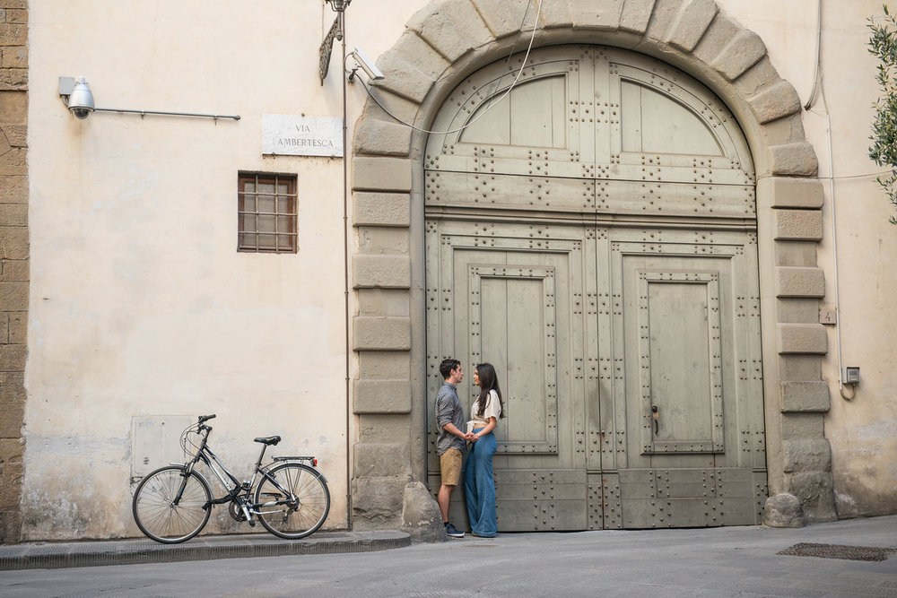 Couple standing together in front of large doorway in Florence, Italy