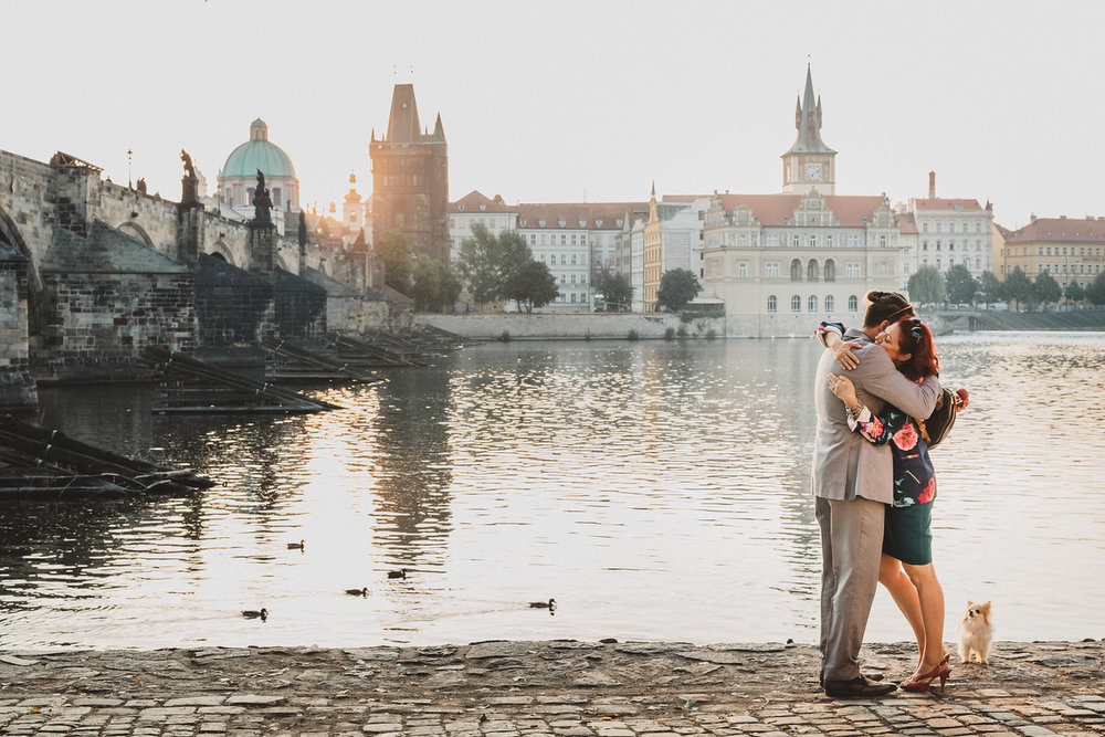 Couple hugging each other after their surprise proposal near a river in Prague, Czech Republic