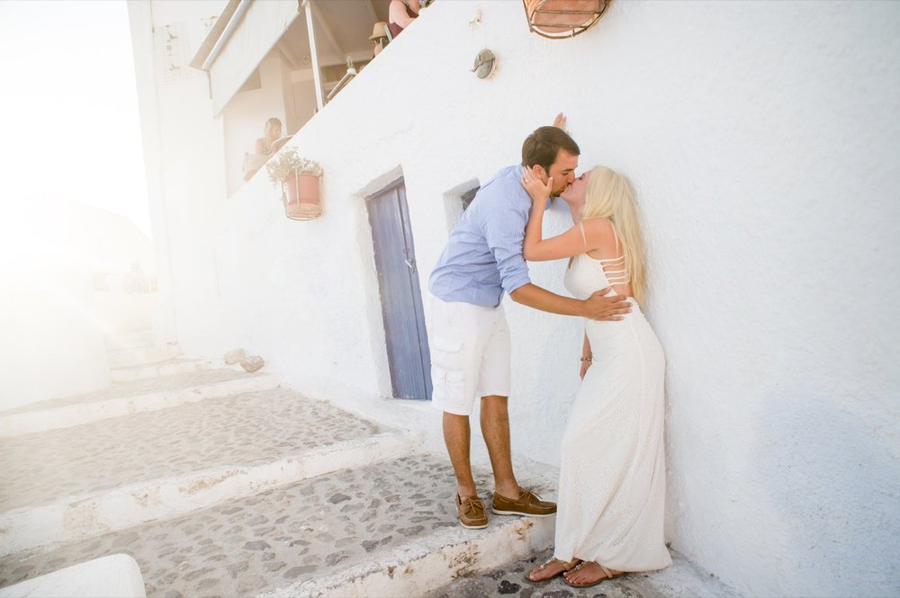Couple kissing each other on a couples trip in Santorini, Greece