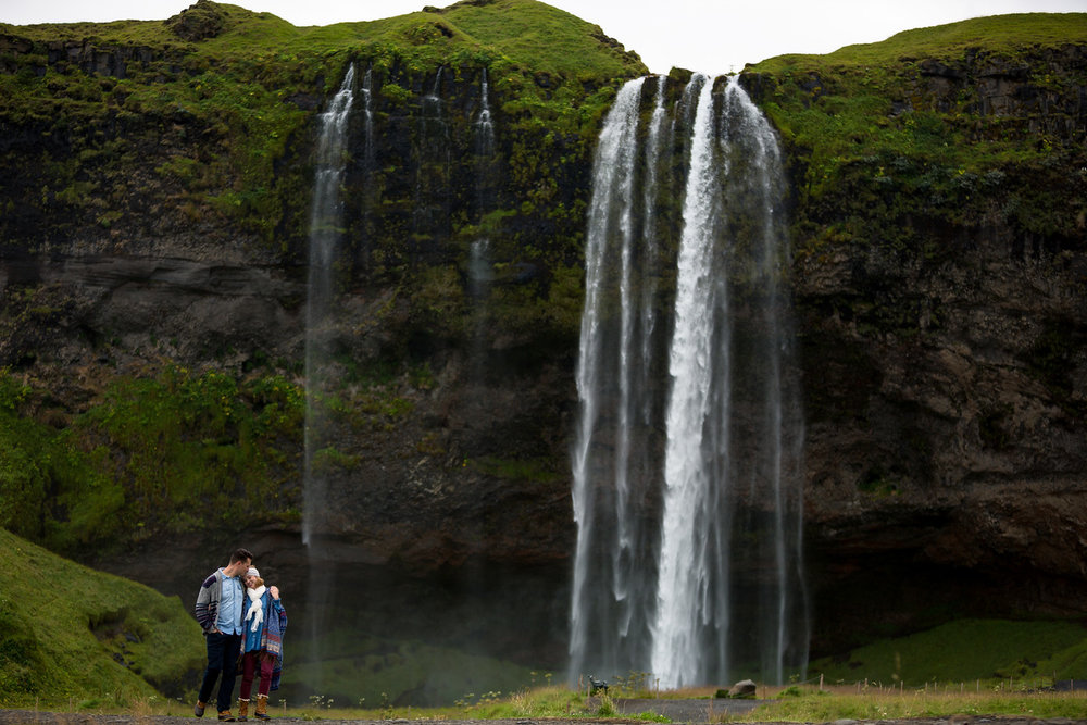 Couple hugging each other in front of waterfall in Reykjavik, Iceland