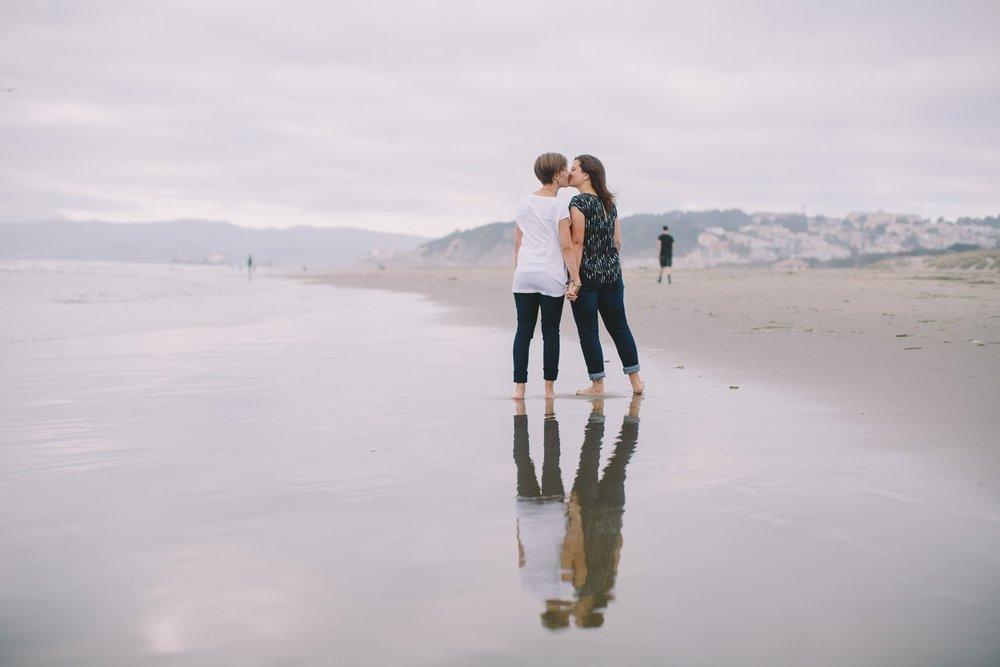 LGBTQ+ couple kissing on a beach in San Francisco, California, USA