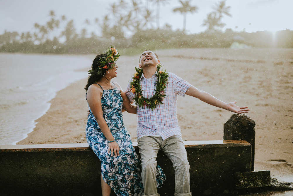 Couple laughing together in the pouring rain in Honolulu, Hawaii USA