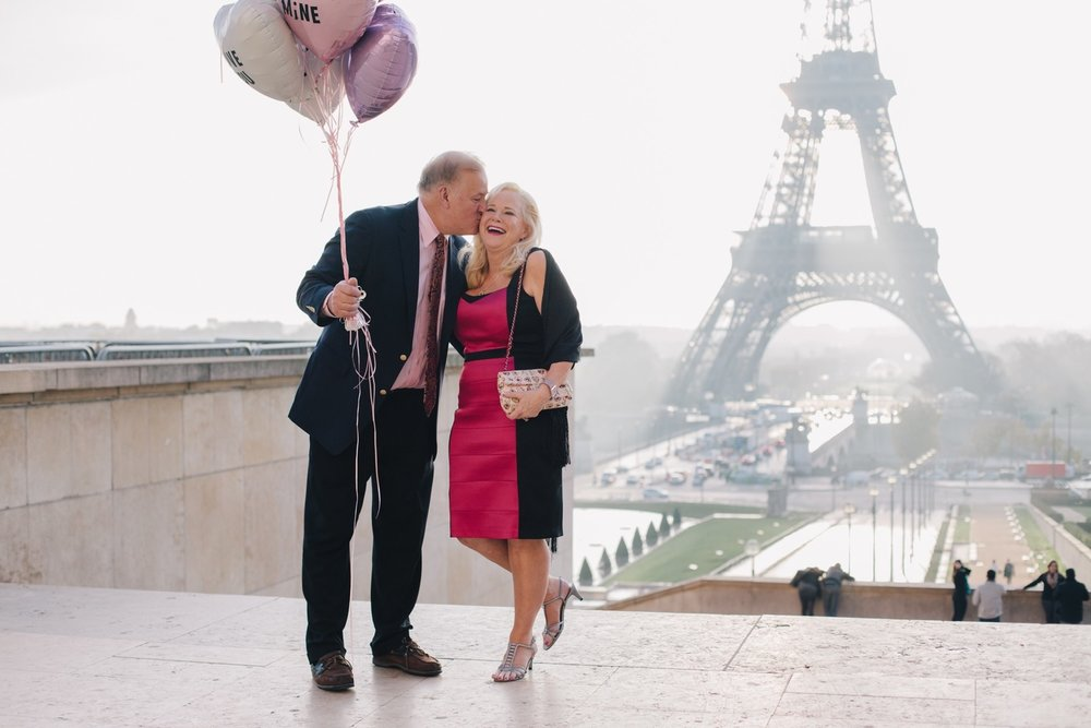 Man kissing his partner's cheek while holding balloons with the Eiffel Tower in the background in Paris, France