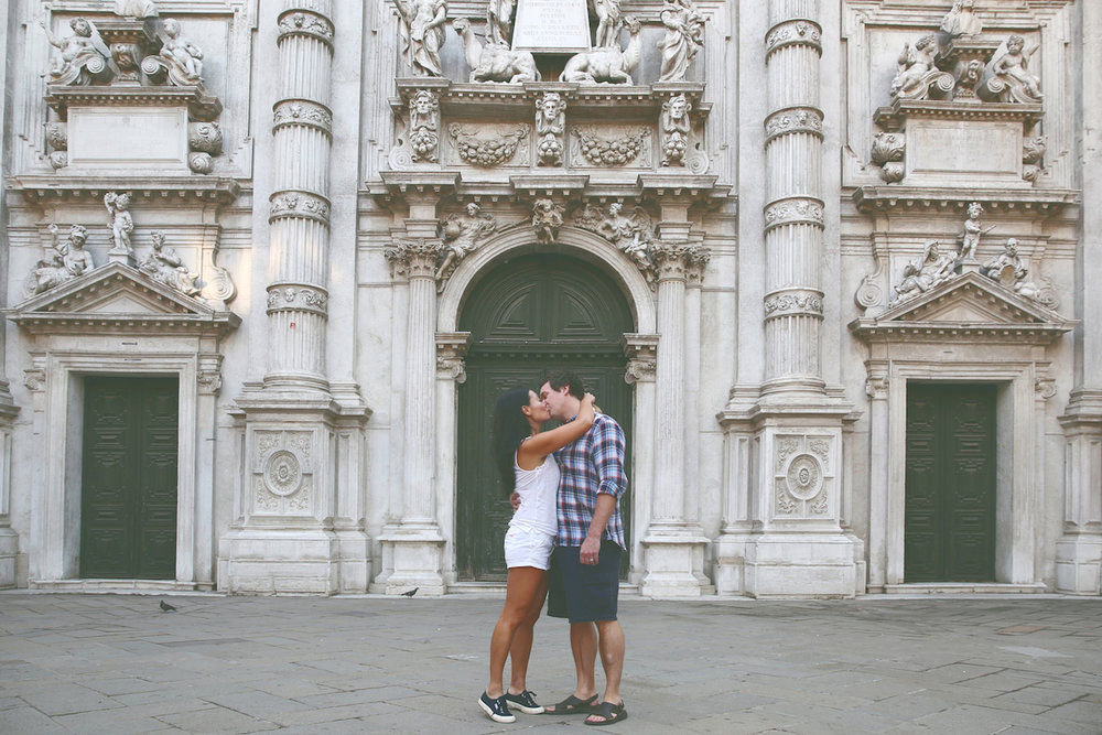 Couple kissing in front of green doorways on a couples trip in Venice, Italy