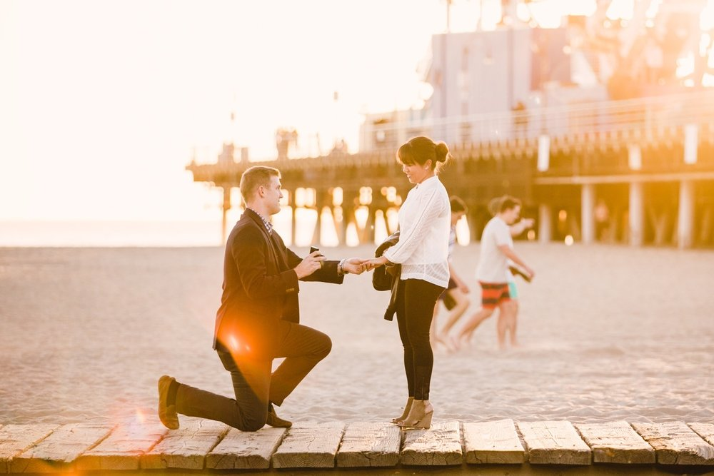 Man proposing to his partner on a boardwalk along a beach in Los Angeles, California USA