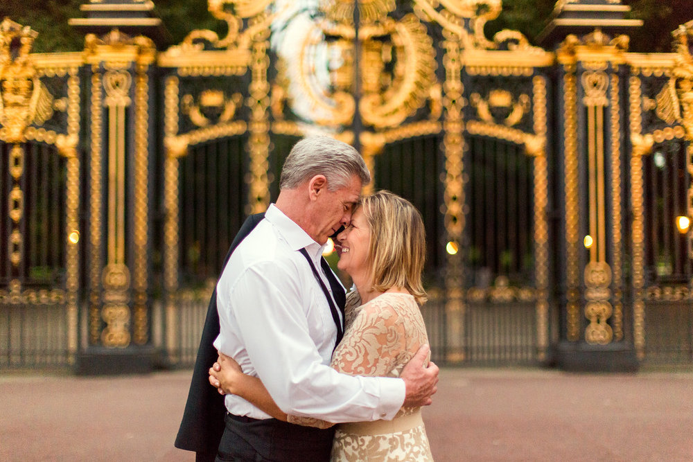 Mature couple hugging each other in front of the gates at Buckingham Palace in London, UK
