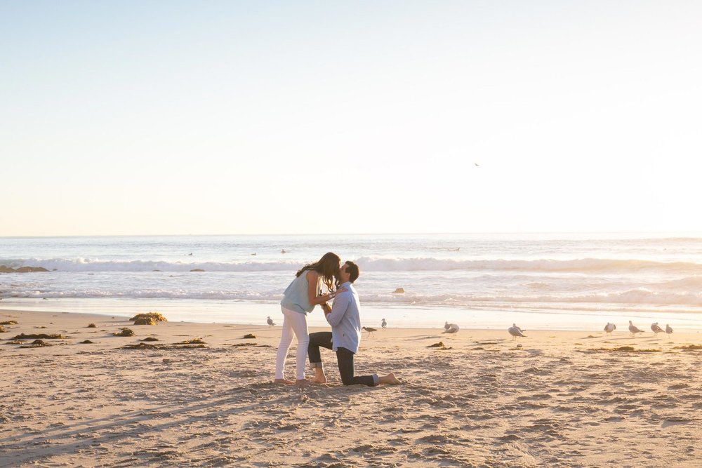 Couple kissing on the beach surrounded by seagulls in Los Angeles, California, USA