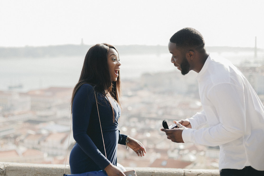 Woman surprised by her partner's surprise proposal as he presents the engagement ring in Lisbon, Portugal