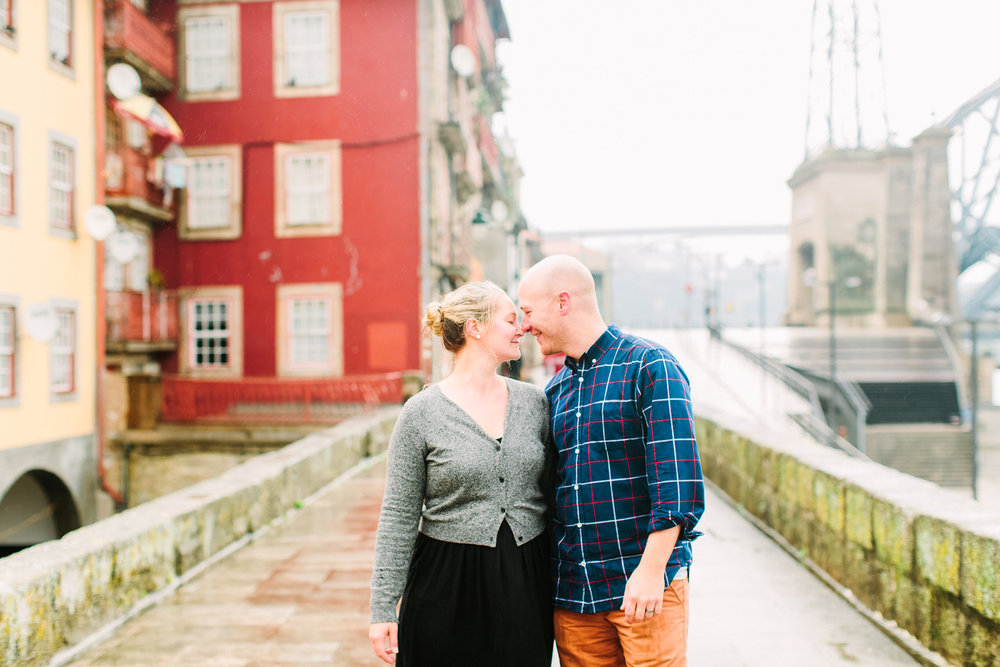 Couple smiling at each other on a bridge walkway on a couples trip in Porto, Portugal