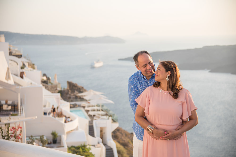 Mature couple holding each other and smiling with the Mediterranean sea in the background in Santorini, Greece