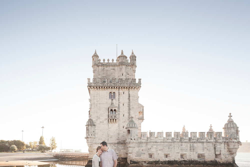 Couple hugging each other in front of castle on a couples trip in Lisbon, Portugal