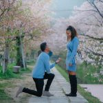 A man proposes to a woman surrounded by cherry blossoms in Kyoto.