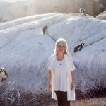 A woman poses in front of penguins on Boulders Beach in Cape Town.