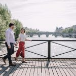 A couple walks hand in hand over a bridge crossing the Seine in Paris.
