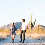 A couple holds hands and walks through the desert in North Scottsdale.